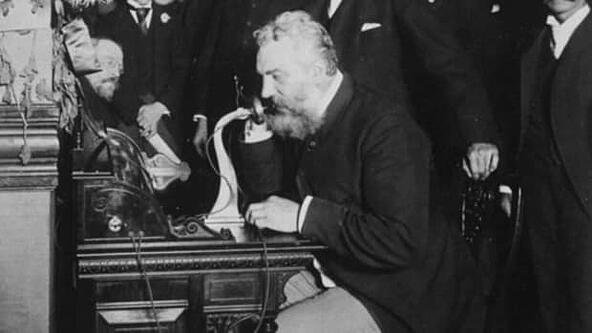 man using first telephone ever invented